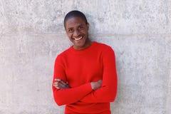 Hombre afroamericano joven que sonríe con los brazos cruzados Fotografía de archivo
