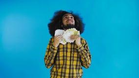 Hombre afroamericano joven que sostiene el dinero del efectivo en fondo azul metrajes