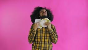 Hombre afroamericano joven que sostiene el dinero del efectivo en fondo p?rpura almacen de video