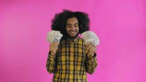 Hombre afroamericano joven que sostiene el dinero del efectivo en fondo p?rpura metrajes