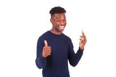 Hombre afroamericano joven que sostiene su smartphone y que hace a Fotografía de archivo