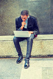 Hombre afroamericano joven que trabaja en el ordenador portátil afuera adentro Foto de archivo libre de regalías
