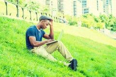Hombre afroamericano joven que trabaja en el ordenador portátil al aire libre adentro Fotos de archivo libres de regalías