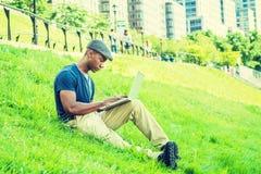 Hombre afroamericano joven que trabaja en el ordenador portátil al aire libre adentro Foto de archivo libre de regalías