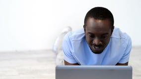 Hombre afroamericano joven que usa el ordenador portátil almacen de video