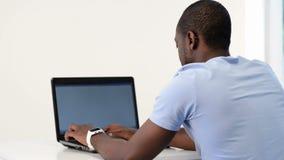 Hombre afroamericano joven que usa el ordenador portátil almacen de metraje de vídeo