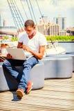 Hombre afroamericano joven que viaja, ordenador portátil de trabajo adentro Imágenes de archivo libres de regalías