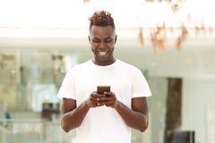 Hombre afroamericano joven sonriente que usa el teléfono móvil que se coloca al aire libre en ciudad Imagenes de archivo