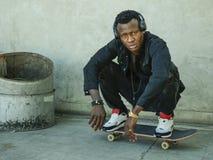 Hombre afroamericano negro atractivo y serio joven que se pone en cuclillas en tablero del patín en la esquina de calle del grung fotos de archivo libres de regalías