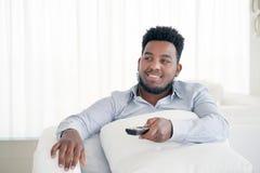 Hombre afroamericano negro hermoso y atractivo joven que sienta en casa la televisión de observación del sofá del sofá usando el  imagenes de archivo