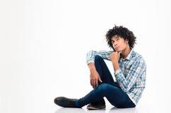 Hombre afroamericano pensativo que se sienta en el piso Imagenes de archivo