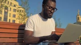 Hombre afroamericano positivo que usa el ordenador para el proyecto al aire libre almacen de video