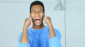 Hombre afroamericano que celebra éxito en su oficina foto de archivo libre de regalías