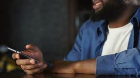 Hombre afroamericano que comunica con los visitantes de la barra que piden el taxi en app del teléfono móvil metrajes