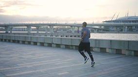 Hombre afroamericano que corre en la acera de la ciudad almacen de metraje de vídeo