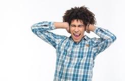 Hombre afroamericano que cubre sus oídos y que grita Imagenes de archivo