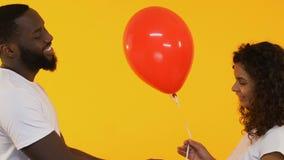 Hombre afroamericano que da el globo a la mujer bonita, saludo del cumpleaños, afecto almacen de video