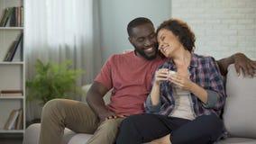 Hombre afroamericano que hace sorpresa a su novia que da su caja con la joya almacen de metraje de vídeo