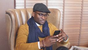 Hombre afroamericano que lleva el sombrero negro, en una silla, cigarro que fuma almacen de metraje de vídeo