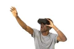 Hombre afroamericano que lleva las gafas de la visión del vr 360 de la realidad virtual que disfrutan del videojuego Imagen de archivo