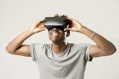 Hombre afroamericano que lleva las gafas de la visión del vr 360 de la realidad virtual que disfrutan del videojuego Foto de archivo libre de regalías