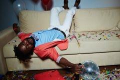 Hombre afroamericano que miente en el sofá Fotos de archivo libres de regalías