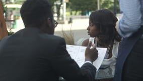 Hombre afroamericano que ordena en café exterior, mientras que se sienta con su socio femenino almacen de video