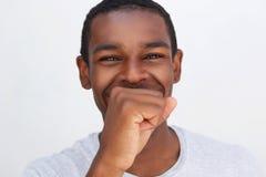 Hombre afroamericano que ríe con la boca de la cubierta de la mano Fotos de archivo