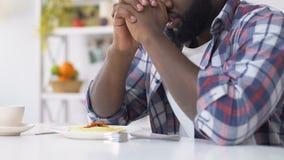 Hombre afroamericano que ruega antes de comer, pidiendo que dios bendiga la comida, fe almacen de metraje de vídeo