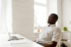 Hombre afroamericano que se relaja después de aire de respiración del trabajo en o casero fotografía de archivo