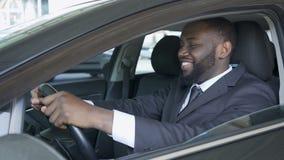Hombre afroamericano que se sienta en el coche costoso satisfecho y que sonríe, prueba de conducción almacen de metraje de vídeo