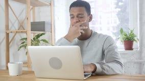 Hombre afroamericano que se sienta en trastorno de la oficina por la pérdida, trabajando en el ordenador portátil almacen de metraje de vídeo