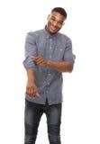 Hombre afroamericano que sonríe y que rueda encima de las mangas Imagenes de archivo