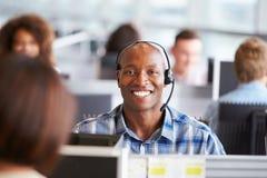 Hombre afroamericano que trabaja en el centro de llamada, miradas a la cámara Imagen de archivo libre de regalías