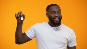 Hombre afroamericano sonriente que señala el finger en llaves de la casa, propiedades inmobiliarias almacen de video