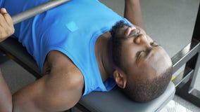 Hombre afroamericano trabajador que levanta el barbell en el club de fitness, deporte almacen de metraje de vídeo