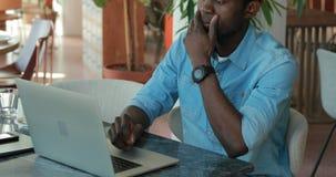 Hombre afroamericano usando el ordenador portátil en el café que comparte ideas del negocio metrajes