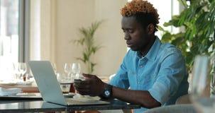 Hombre afroamericano usando el ordenador portátil en llamada del café por el teléfono móvil almacen de video