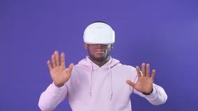 Hombre afroamericano usando las auriculares de la realidad virtual aisladas sobre el fondo violeta almacen de metraje de vídeo