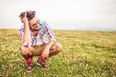 Hombre agachado de risa que pasa su mano a través de su pelo Fotografía de archivo libre de regalías