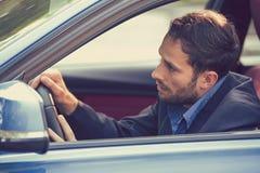 Hombre agotado cansado soñoliento de la opinión de ventana lateral que conduce su coche fotos de archivo libres de regalías
