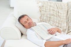 Hombre agotado que duerme en el sofá Foto de archivo libre de regalías