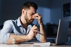 Hombre agotado que trabaja en horas extras en oficina oscura Imágenes de archivo libres de regalías