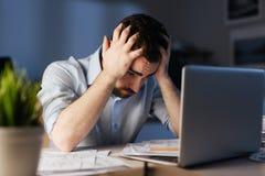Hombre agotado que trabaja horas adicionales en oficina de la noche Fotos de archivo