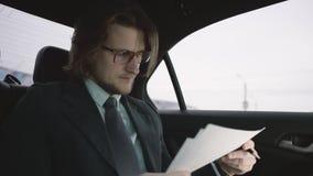 Hombre agradable con el pelo marrón en la camisa del pistacho y traje gris y vidrios que montan en coche y que leen documentos almacen de metraje de vídeo