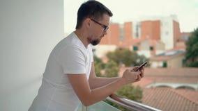 Hombre agradable con el teléfono móvil en balcón almacen de video