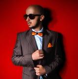 Hombre agradable en gafas de sol y traje en fondo rojo Foto de archivo libre de regalías