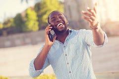 Hombre agradable encantado que sostiene su smartphone cerca del oído Imagenes de archivo