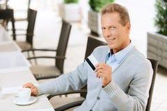Hombre agradable que se sienta en la tabla Imágenes de archivo libres de regalías