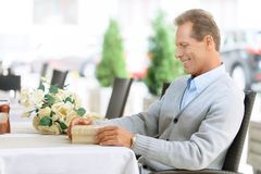 Hombre agradable que se sienta en la tabla Imagen de archivo